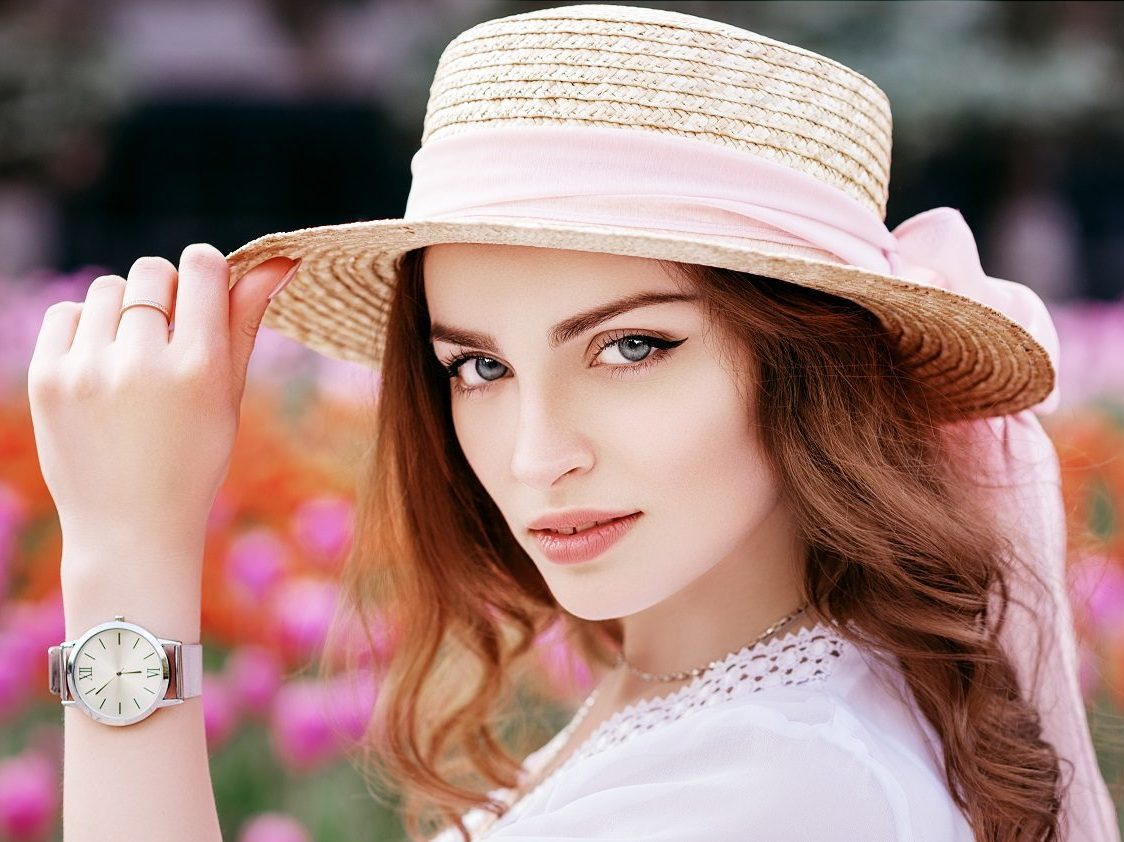 Beautiful girl wearing straw hat, wrist watch, blouse posing near tulips